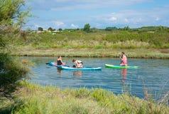 Jongeren die doend tribune op peddel op een kalme rivier op hete de zomerdag genieten van stock foto's