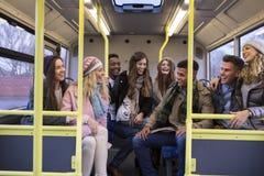 Jongeren die door bus samen reizen stock afbeeldingen