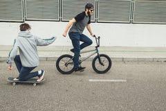 Jongeren die fietsen en skateboards in de stad berijden Kerels met een vleet en een bmx onderaan de straat royalty-vrije stock fotografie