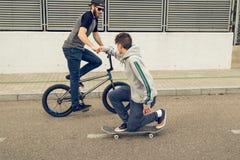 Jongeren die fietsen en skateboards in de stad berijden Kerels met een vleet en een bmx onderaan de straat stock fotografie