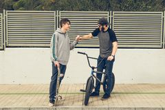 Jongeren die fietsen en skateboards in de stad berijden Kerels met een vleet en een bmx onderaan de straat stock afbeeldingen