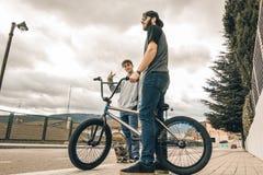Jongeren die fietsen en skateboards in de stad berijden Kerels met een vleet en een bmx onderaan de straat stock foto