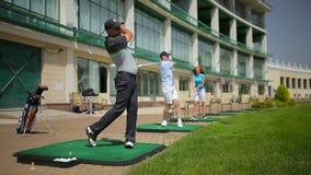 Jongeren die golf spelen dichtbij het clubhuis stock videobeelden