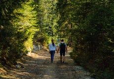 Jongeren die langs een bergweg lopen en handen, concept houden het reizen in de wildernis, exemplaarruimte, stock foto