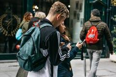 Jongeren die onderaan de straat lopen en mobiele telefoons met behulp van royalty-vrije stock afbeeldingen