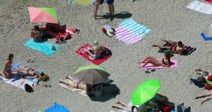 Jongeren die op het strand zonnebaden stock video