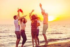 Jongeren die op Strand bij Zonsondergang dansen royalty-vrije stock afbeeldingen
