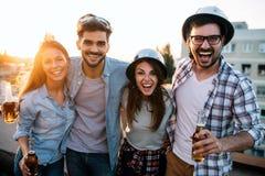 Jongeren die op terras met dranken bij zonsondergang partying royalty-vrije stock foto