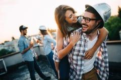 Jongeren die op terras met dranken bij zonsondergang partying royalty-vrije stock foto's