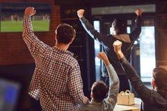 Jongeren die op voetbal op TV in de bar letten stock afbeelding