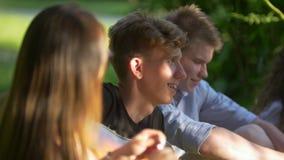 Jongeren die openluchtspelen spelen die pret in de zomerpark hebben stock videobeelden