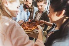 Jongeren die pizza eten Stock Fotografie