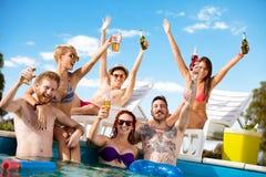 Jongeren die pret in pool met dranken in wapens hebben royalty-vrije stock foto's