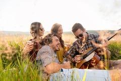 Jongeren die samen in gras het spelen gitaar zitten royalty-vrije stock foto