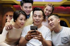 Jongeren die smartphone van vriend bekijken stock afbeelding
