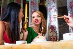 Jongeren die sushi in Aziatisch restaurant eten Royalty-vrije Stock Foto