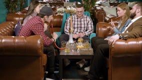 Jongeren die waterpijp roken en in een koffie rusten stock video