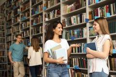 Jongeren die zich dichtbij boekenrekken bevinden stock afbeelding