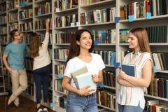 Jongeren die zich dichtbij boekenrekken bevinden stock foto
