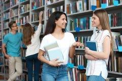 Jongeren die zich dichtbij boekenrekken bevinden stock afbeeldingen