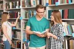 Jongeren die zich dichtbij boekenrekken bevinden royalty-vrije stock afbeelding