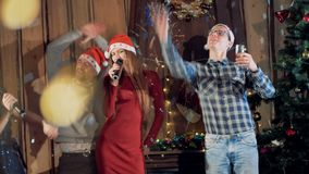 Jongeren het dansen het zingen bij Nieuwjaarpartij die Kerstmishoeden dragen Langzame Motie 4K stock video