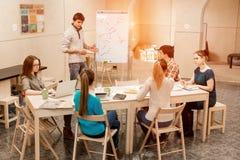 Jongeren het luisteren Presentatie van mannelijke Manager stock fotografie