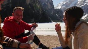 Jongeren het reizen Drie vrienden die een picknick op de kust hebben en sandwiches eten stock video
