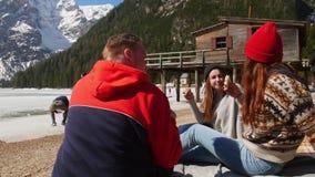 Jongeren het reizen Vrienden die een picknick op de kust hebben en sandwiches eten stock footage