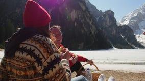 Jongeren het reizen Vrienden die een picknick op de kust hebben en sandwiches eten rond bergen stock video