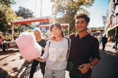 Jongeren met katoen candyfloss bij pretpark stock foto