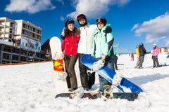 Jongeren in ski-kostuums en skibeschermende brillen die pret hebben terwijl tribune stock foto