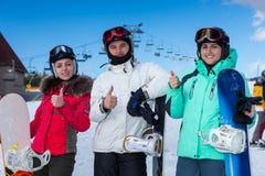 Jongeren in ski-kostuums, helmen en van skibeschermende brillen duim-omhooggaande whi royalty-vrije stock foto's
