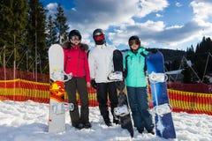 Jongeren in skikostuums, helmen en skibeschermende brillen die bevinden zich met stock foto