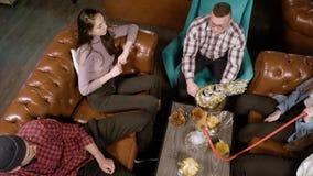 Jongerenvrienden die waterpijp roken en in een koffie rusten stock videobeelden