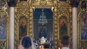 Jonggehuwden bij het huwelijk in de Orthodoxe Kerk stock videobeelden