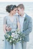 Jonggehuwden die bij de kust knuffelen stock afbeeldingen
