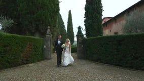Jonggehuwden die de tuin van holdingshanden lopen stock video