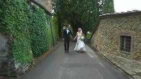 Jonggehuwden die langzame holdingshanden lopen stock video