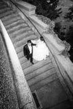 Jonggehuwden die onderaan bw van steenstappen lopen Stock Foto