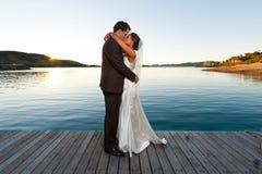 Jonggehuwden die op een pier bij zonsondergang kussen Stock Fotografie