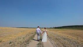 Jonggehuwden die op het gebied lopen stock video