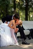 Jonggehuwden die op parkbank kussen Royalty-vrije Stock Foto's
