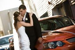 Jonggehuwden die tegen een huwelijksauto omhelzen Stock Fotografie