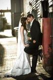 Jonggehuwden die tegen een rode doos omhelzen Royalty-vrije Stock Afbeeldingen