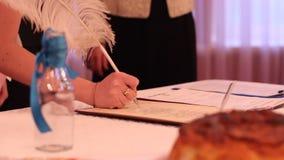 Jonggehuwden die verwezenlijking van nieuwe familie bevestigen door huwelijksakte te ondertekenen stock video