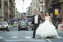 Jonggehuwden die zich bij de voetgangersoversteekplaats bevinden Royalty-vrije Stock Afbeelding