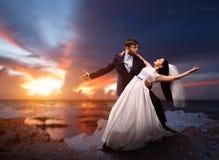 Jonggehuwden het dansen, overzees en zonsondergang op achtergrond Royalty-vrije Stock Fotografie