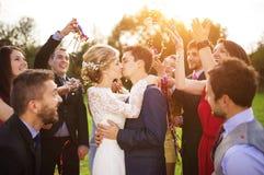 Jonggehuwden met gast op hun tuinpartij Stock Foto's