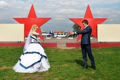 Jonggehuwden op een achtergrond van rode sterren Royalty-vrije Stock Foto